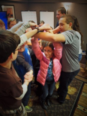 A sibling group works through an ice breaker exercise of untying the knot without breaking the circle at the the Carolinas Down Syndrome Conference.