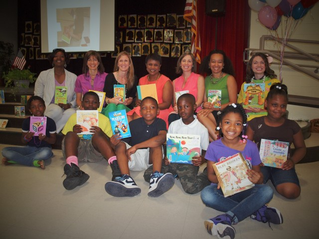 Students pose with books and Big Read Event presenters. Back row-left to right- Sedgefield Principal Ivy Gill, ALP Director Allison Houser, Laurie Martin, Owner of Simplicity Organizers; Sonja Gantt, WCNC; Blair Kingsbury Oliver, Simplicity Organizers; Sophia Crawford, Sedgefield Literacy Coach; Brennan Sheare, Promising Pages' Erma the Bookworm.