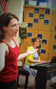 : Pictured left to right: Director Beverly Warkulwiz and Pianist Amber Faulhaber work with the singers to improve sections of songs.